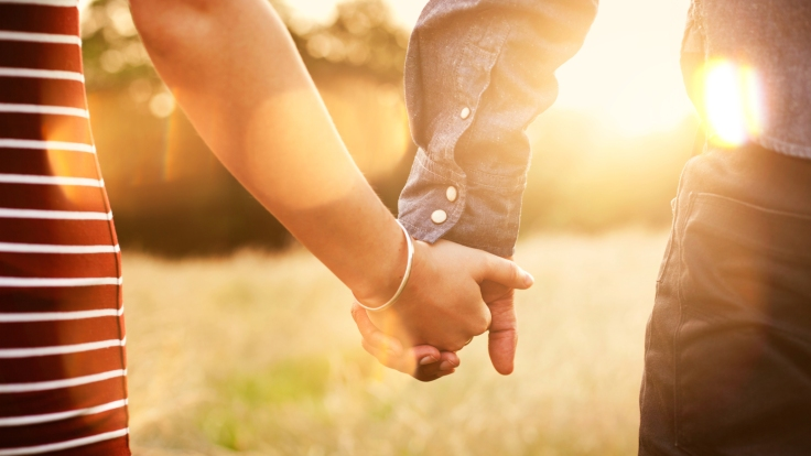 Young couple holding hands with sun-flare.
